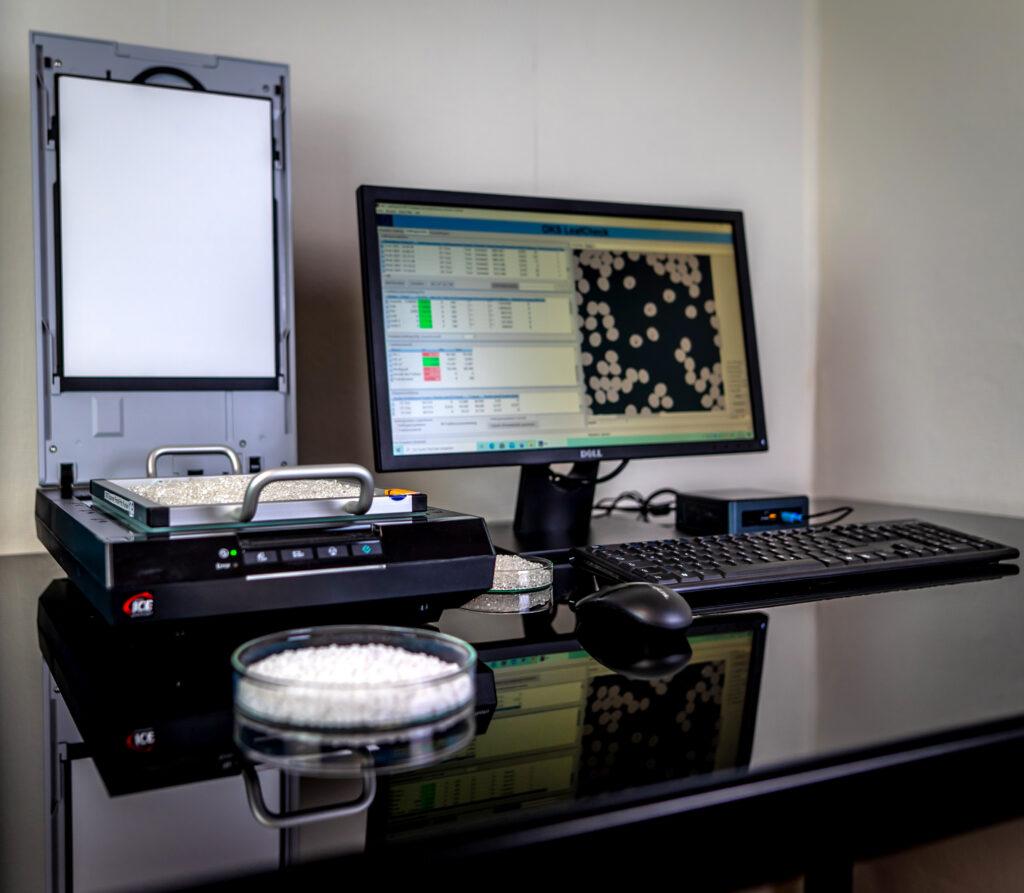 Exemplarischer Aufbau des Scanner-Systems, links ein aufgeklappter Scanner, rechts in Monitor, Petrischale mit Kunststoff im Vordergrund, Maus und Tastatur